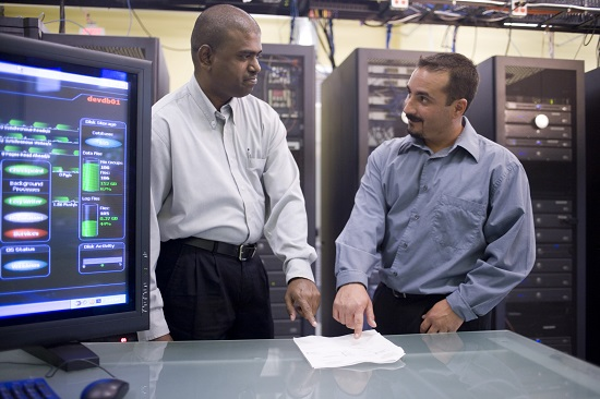 computer workers standing in front of network servers