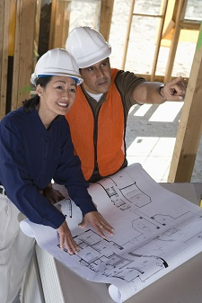 Architect and construction manager looking at blueprints