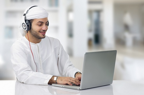 Man with headphones on a computer