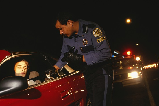 Police officer stopping a car at night