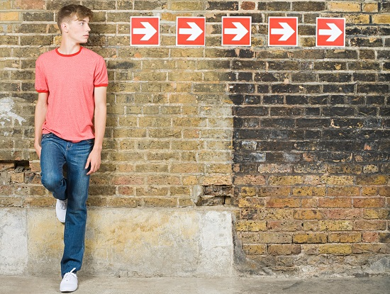 Young man standing against a wall with arrows