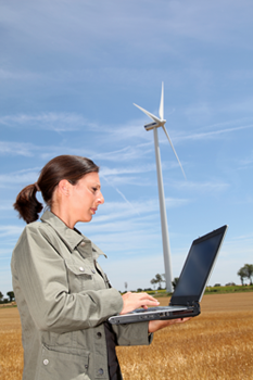 Woman with computer in front of wind turbine