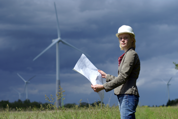 Woman with blueprints in front of wind turbine