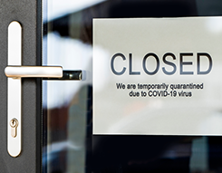 Closed sign posted on business entry door (due to covid-19)