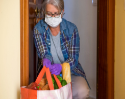 Woman wearing face mask with bag of groceries