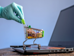 Gloved hand, shopping cart, and laptop computer