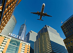 Airplane flying over a hotel.