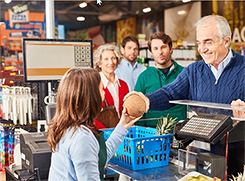 Older gentleman purchasing groceries at the cash register