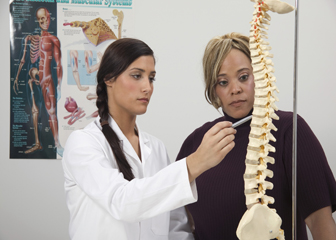A photo of a chiropractor and her patient reviewing the issue with the bulge in her spine.