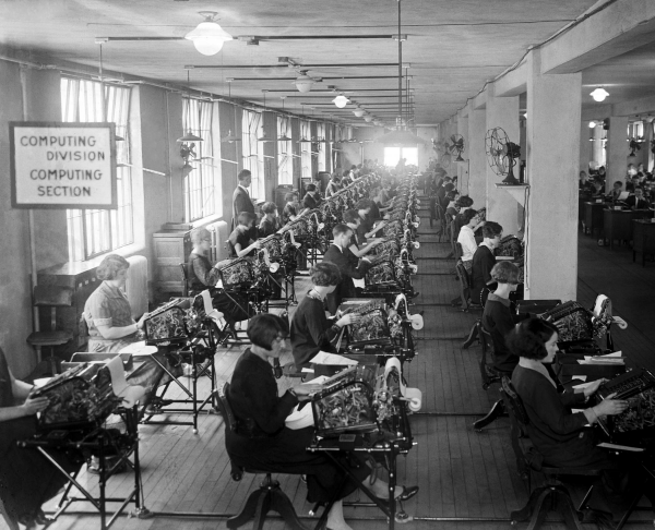 Image of female workers using calculating machines