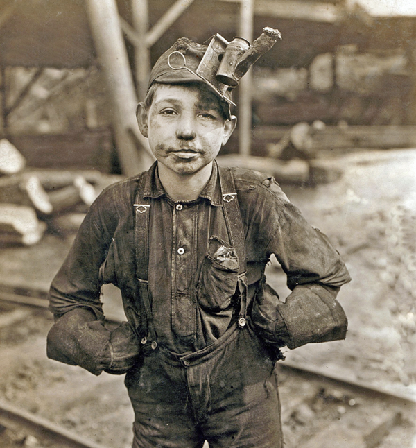 Tipple boy at West Virginia coal mine worked with the tipple, a device that tilted coal cars from the mine for unloading. Photo by Lewis Hine, 1908. Copyright: Everett Historical.