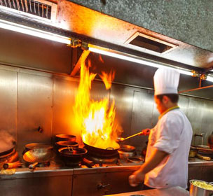 Chef cooking on stove in restaurant