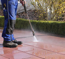 Worker power washing surface
